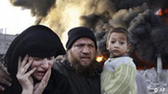 A Palestinian family rushes past a burning building in the Gaza Strip