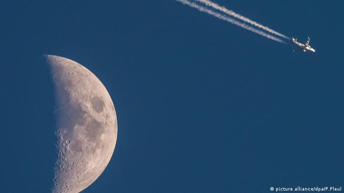 A plane in the sky, with half the moon in the foreground