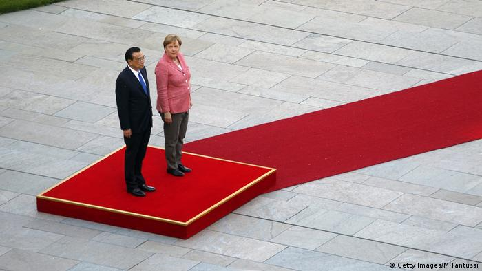 German Chancellor Angela Merkel and Chinese Prime Minister Li Keqiang stand on a podium to listen to the national anthems at the Chancellery