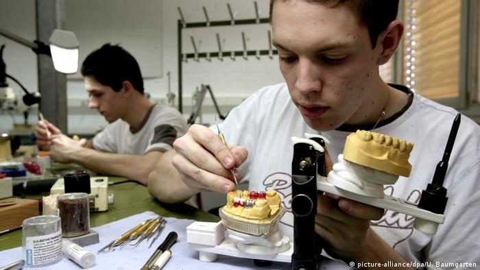 A person working on a teeth prosthesis (picture-alliance/dpa/U. Baumgarten)