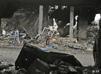Palestinians inspect the rubble of a building in the Gaza Strip