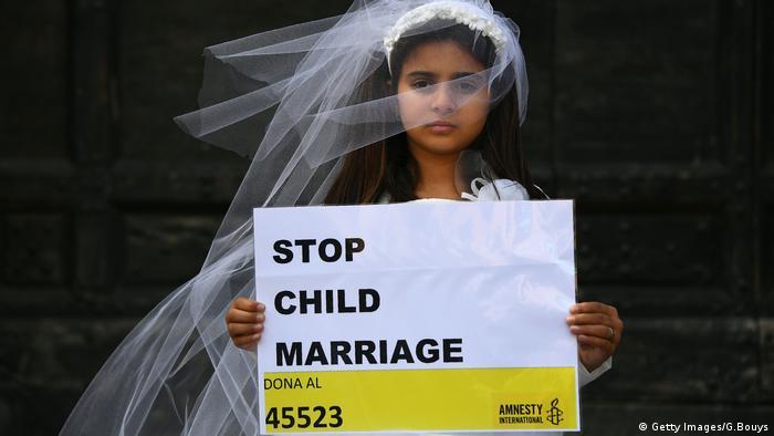 Menina vestida de noiva ergue cartaz Parem com casamento infantil