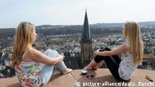 ARCHIV - Nancy und Angie sitzen am 27.03.2012 auf einer Mauer hoch über Marburg mit Blick auf die Lutherkirche. Studentenleben und Forscherdrang gehören seit dem 16. Jahrhundert zu Marburg. Deswegen will sich die mittelhessische Universitätsstadt unter dem Motto «Universitätsstadt als kultureller Raum über 500 Jahre» um die Aufnahme ins Unesco-Welterbe bewerben.Foto: Uwe Zucchi dpa/lhe (zu lhe-BLICKPUNKT vom 06.07.2012) +++(c) dpa - Bildfunk+++ | Verwendung weltweit