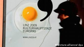 A man walks by a poster for Linz as cultural capital that has a fried egg on it