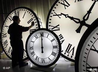 A man cleans a giant clock face. Next to it are other clocks.