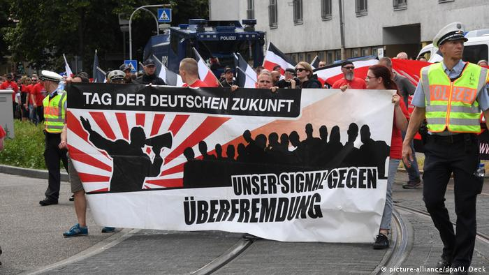 Right-wing extremists demonstrators march with a banner protesting cultural infiltration (picture-alliance/dpa/U. Deck)