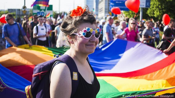 Eine Frau mit einer bunten Sonnenbrille vor einem großen Tuch in Regenbogenfarben (Foto: Picture Alliance)