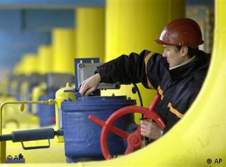 A worker operates a valve at a gas storage and transit point