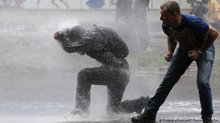 Protester hit by a jet from a water cannon