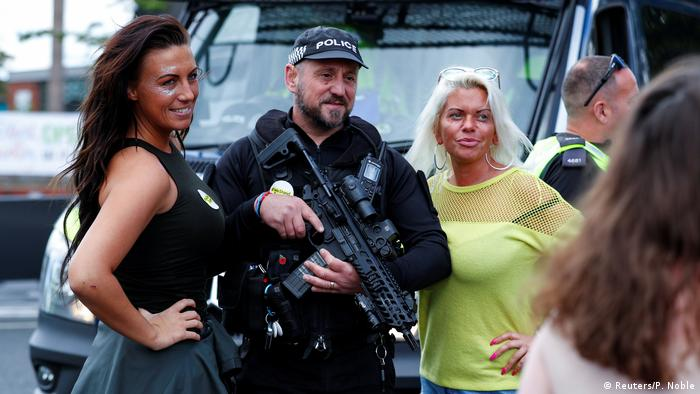 Armed policeman poses with fans