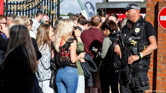 Policeman stands with fans at Old Trafford