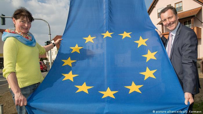 Duas pessoas seguram uma bandeira da União Europeia