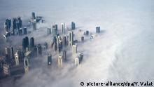 ARCHIV 2014 +++ FILE - An aerial view of high-rise buildings emerging through fog covering the skyline of Doha, as the sun rises over the city, in Doha, Qatar, 15 February 2014. EPA/YOAN VALAT (zu dpa Diskrete Investoren aus Katar - Kleines Emirat mit großem Appetit vom 20.05.2014) +++(c) dpa - Bildfunk+++ |