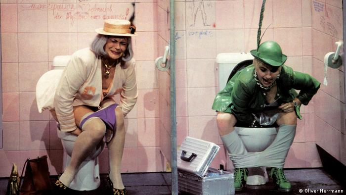 Actresses Kirsten Dene and Maria Happel playing in Elfriede Jelinek's Raststätte - sitting on toilets on the stage (Photo: Oliver Herrmann)