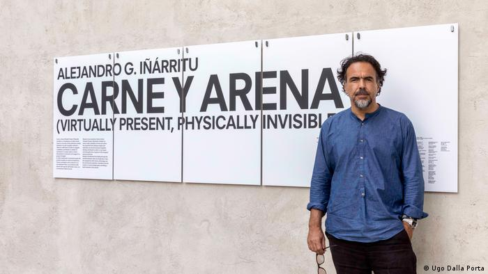 Alejandro G. Inarritu stands in front of a sign advertising his film (Ugo Dalla Porta)