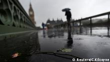 A man walks past a flower in a puddle next to newly installed security barriers on a wet and windy morning on Westminster Bridge, in London, Britain, June 6, 2017. REUTERS/Clodagh Kilcoyne