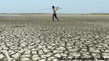 An Indian man walks over the parched bed of a reservoir on the outskirts of Chennai (Getty Images/AFP/A. Sankar)