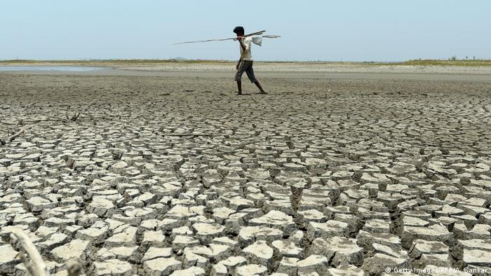 A man walks over parched earth (photo: Getty Images/AFP/A. Sankar)
