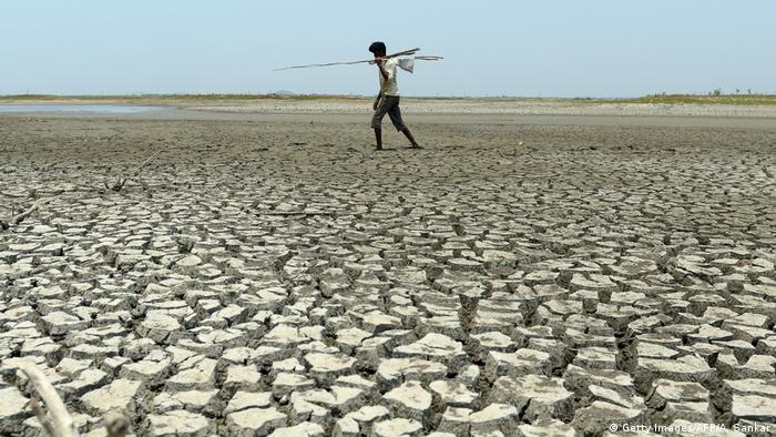 A man walks across cracked earth