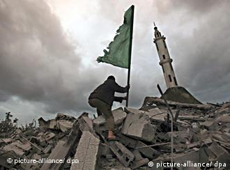 A Palestinian puts a Hamas flag on the remains of the destroyed Abu Hanifa mosque following Israeli airstrikes in the Tal al Hawa area, south of Gaza City, Dec. 31.