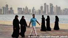 FILE- In this Saturday, April 7, 2012 file photo, the new high-rise buildings of downtown Doha, photographed in the background as Qatari women and a man walk by the sea in Doha, Qatar. Qatar, now facing a diplomatic crisis with other Arab nations, is a small country with a big history of turmoil and coups as it became one of the world's top suppliers of natural gas and now plans to host the 2022 FIFA World Cup. (AP Photo/Kamran Jebreili, File) |