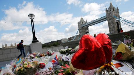 Flowers, flags and balloons memorialized the victims of a truck attack with London Bridge in the background.