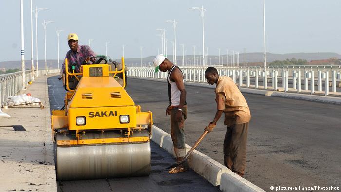 Three men use a paving machine to tar a road in Mali's capital Bamako