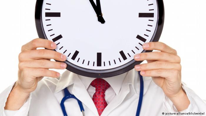 Symbolic image of doctor holding up clock over his head (Copyright: picture-alliance/blinkwinkel