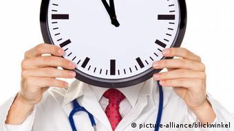 Arzt im Stress mit Uhr vor Kopf (picture-alliance/blickwinkel)