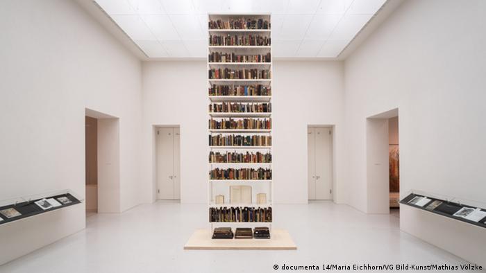 Ausstellungsansicht mit einem Bücherregal in einem weißen Raum