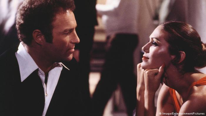 Film still 'Rollerball': a man and a woman looking at each other.