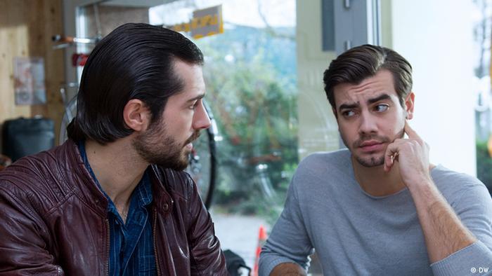 Zwei Männer sitzen sich gegenüber und schauen sich an