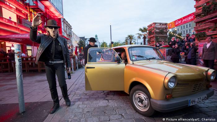 Udo Lindenberg holds a bottle of beer on the Reeperbahn, an East German Trabant car off to the side (Picture alliance/dpa/C. Charisius)
