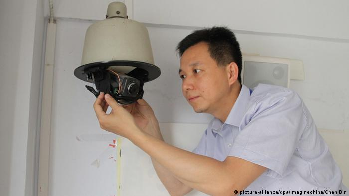 A Chinese invigilator installs a surveillance camera in a classroom ahead of the national college entrance