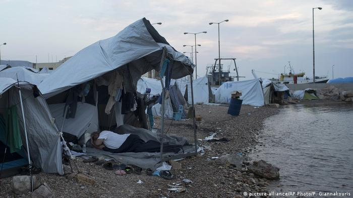 Refugees sleep outside a tent at a beach near a refugee camp in Chios