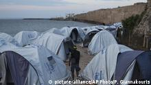 A migrant from Morocco walks among tents at a beach outside the Souda refugee camp in front of a stone wall of the castle of Chios island, Greece, Friday, June 9, 2017. The International Organization for Migration says more than 60,000 migrants have reached the shores of Europe so far in 2017, a sizable decrease compared to the same period last year. (AP Photo/Petros Giannakouris) |