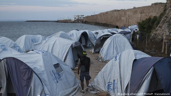 A migrant walks among tents at a beach outside a refugee camp next to the water on Chios