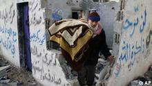 A Palestinian man carries a blanket from a destroyed house that was hit in an Israeli missile strike in the Rafah refugee camp southern Gaza Strip, Friday, Jan. 2, 2009. Israel showed no sign of slowing a blistering seven-day offensive against Gaza's Hamas rulers, destroying homes of more than a dozen of the group's operatives Friday and bombing one of its mosques a day after a deadly strike killed a prominent Hamas figure. (AP Photo/Khaled Omar)