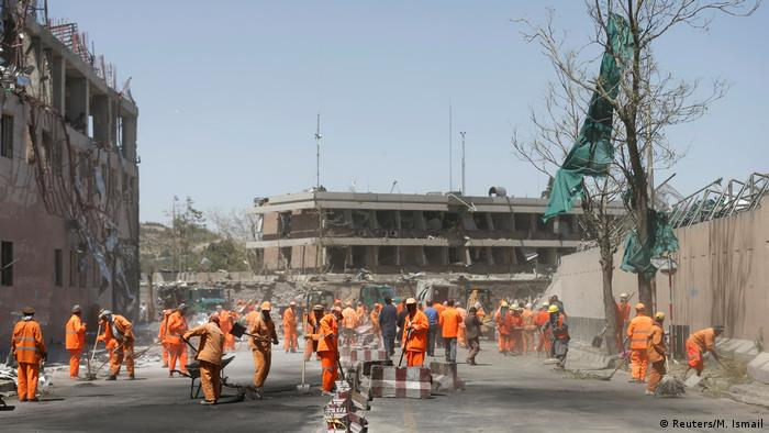 Afghan municipality workers sweep a road outside the German embassy after a blast in Kabul, Afghanistan (Reuters/M. Ismail)