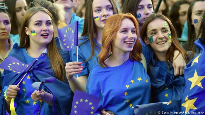 People wave European Union flags during a mass open-air concert on European Square in Kiev