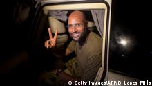 August 23, 2011***Saif al-Islam Kadhafi, son of Libyan leader Moamer Kadhafi, flashes the V-sign for victory as he appears in front of supporters and journalists in the Libyan capital Tripoli in the early hours of August 23, 2011. Seif al-Islam, wanted by the International Criminal Court for crimes against humanity and who ICC prosecutor Luis Moreno-Ocampo earlier said had been arrested by the rebels, claimed the insurgents had suffered heavy casualties when they stormed Kadhafi's Bab al-Azizya compound in Tripoli. AFP PHOTO/ POOL / Dario Lopez-Mills (Photo credit should read DARIO LOPEZ-MILLS/AFP/Getty Images)