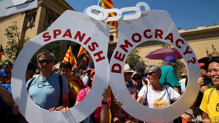 Demonstrators for an independent Catalonia hold up a sign shaped like handcuffs that reads Spanish democracy