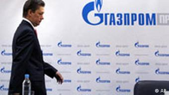 Alexei Miller walking to a Gazprom-decorated podium
