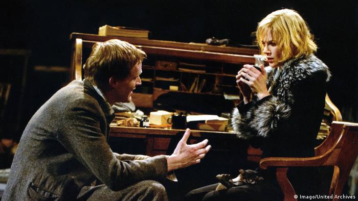 Film still Dogville with Nicole Kidman sitting in a chair with a cup of coffee, in front of her, an actor (Imago/United Archives)
