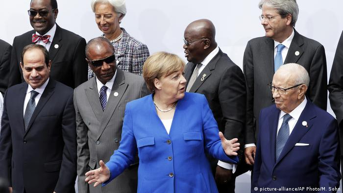 German Chancellor Angela Merkel surrounded by African and European delegates at the G20 Africa Summit in Berlin.