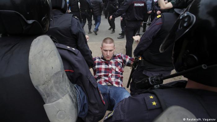 Полицейские несут мужчину на акции протеста в Петербурге