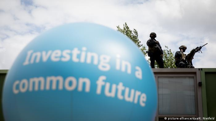 In the foreground, a balloon advertises the summit's slogan: 'Investing in a common future,' while security forces are poised in the background.