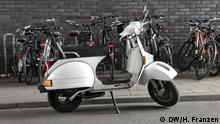 Vespa PX 80 E vor einer Reihe geparkter Fahrräder. Rechte: Harald Franzen / DW