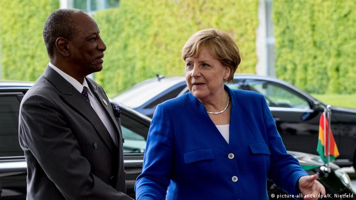 German chancellor Angela Merkel shaking hands with Guinea's president Alpha Conde ahead of the G20 Africa summit last year