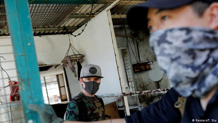 Two men, one wearing a surgical mask, the other a bandana covering mouth and nose (Reuters/T. Siu)